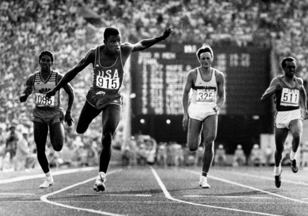 U.S. athlete Carl Lewis (915) flies over the finish line to win the 200-meter run of the Olympic Games at Memorial Coliseum in Los Angeles, Aug. 9, 1984.  From left to right:  Joao Batista of Brazil, Lewis, Ralf Luebke of West Germany and Pietro Mennea of Italy.  (AP Photo/Pool)
